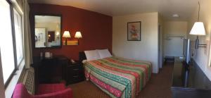 A bed or beds in a room at Hilltop Inn & Suites