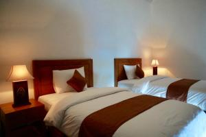 A bed or beds in a room at Gangga Guest House