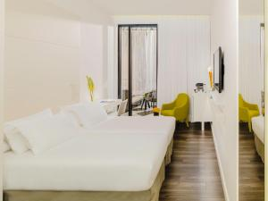 A bed or beds in a room at H10 Urquinaona Plaza