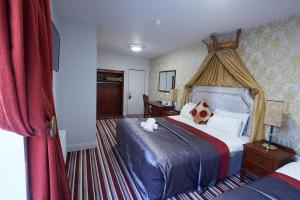 A bed or beds in a room at Killarney Inn