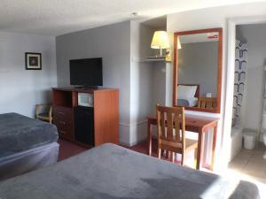 Una televisión o centro de entretenimiento en Swiss Cottage Inn