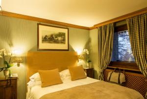 A bed or beds in a room at Hotel Hermitage Relais & Châteaux
