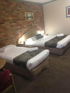 A bed or beds in a room at Pines Country Club Motor Inn