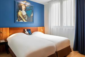 A bed or beds in a room at Hotel des Lys