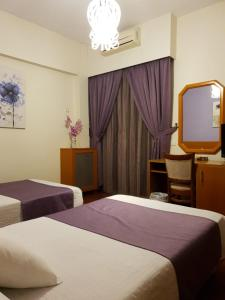 A bed or beds in a room at Ahiram Hotel Byblos