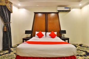 سرير أو أسرّة في غرفة في OYO 131 Al Hamra Palace Al Jawazat Branch