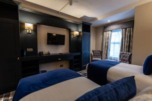 A bed or beds in a room at Fir Trees Hotel