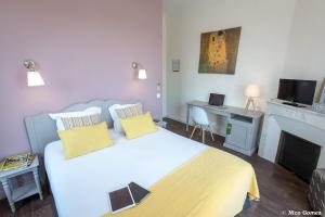 A bed or beds in a room at Le Thimothée : Hôtel & Studios