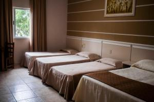 A bed or beds in a room at Pousada Cataratas