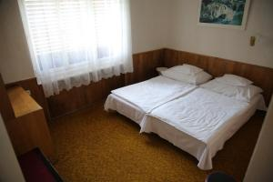 Postel nebo postele na pokoji v ubytování Simply Szálló