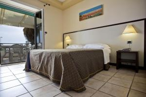 A bed or beds in a room at Cala Saracena Resort
