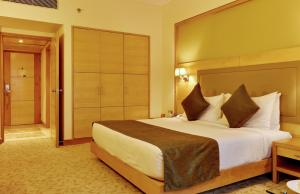 A bed or beds in a room at The Suryaa New Delhi