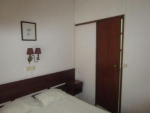 A bed or beds in a room at Pensão Residencial Luanda