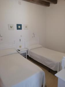 A bed or beds in a room at Hostal Sierpes