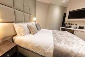 A bed or beds in a room at The Crescent Hyde Park