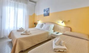 A bed or beds in a room at Hotel Montebello Riccione