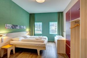 A bed or beds in a room at MEININGER Hotel Amsterdam City West