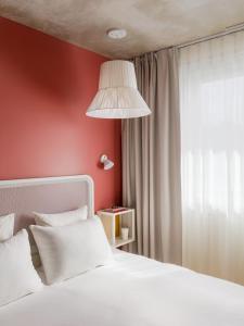 A bed or beds in a room at OKKO Hotels Paris Gare de l'Est