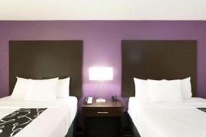 A bed or beds in a room at La Quinta by Wyndham Orlando Universal area