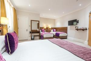 A bed or beds in a room at London House Hotel