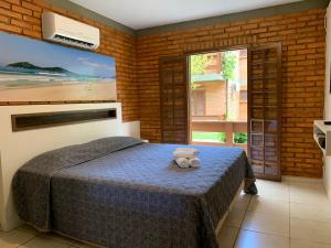 A bed or beds in a room at Hotel São Sebastião da Praia