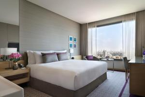 A bed or beds in a room at Avani Plus Riverside Bangkok Hotel -SHA Certified