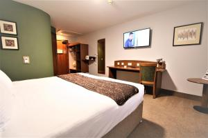 A bed or beds in a room at Doncaster International Hotel by Roomsbooked
