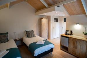 A bed or beds in a room at Pension de Wadvaarder