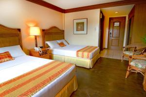A bed or beds in a room at Boracay Tropics Resort Hotel
