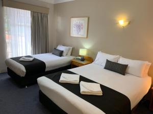 A bed or beds in a room at Heritage Motor Inn Goulburn