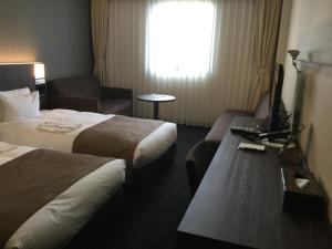 A bed or beds in a room at Hotel Folkloro Kakunodate