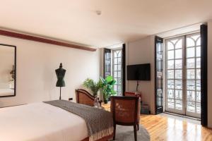 Una televisión o centro de entretenimiento en The House of Sandeman - Hostel & Suites