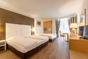 A bed or beds in a room at Business Resort Parkhotel Werth