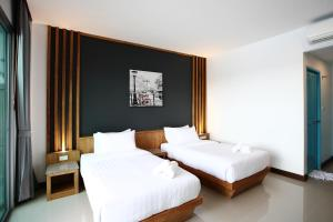 A bed or beds in a room at The Malika Hotel - SHA Plus
