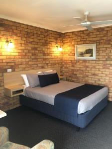 A bed or beds in a room at Ocean View Motor Inn Merimbula