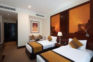 سرير أو أسرّة في غرفة في Landmark Premier Hotel