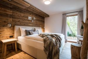 A bed or beds in a room at Les Dolomites Mountain Lodges