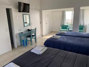 A bed or beds in a room at Axiothea Hotel