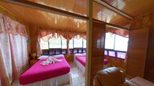 A bed or beds in a room at The Naturalist Beach Resort