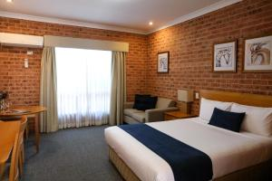 A bed or beds in a room at Akuna Motor Inn and Apartments
