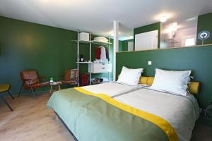 A bed or beds in a room at Hotel Lodge La Petite Couronne