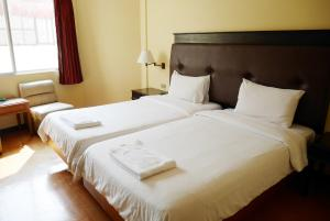A bed or beds in a room at Roma Hotel