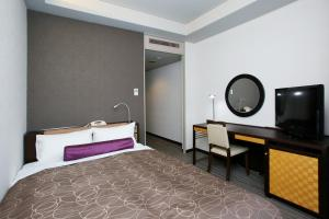 A bed or beds in a room at KKR Hotel Hakata