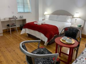 A bed or beds in a room at Savoy Hotel Beaufort-West