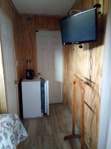 Una televisión o centro de entretenimiento en Alojamiento El Aromo
