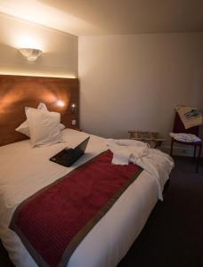 A bed or beds in a room at Hotel & Résidence Les Vallées Labellemontagne