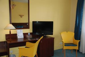 A television and/or entertainment center at The Originals City, Hôtel Cathédrale, Lisieux (Inter-Hotel)