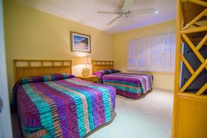 A bed or beds in a room at Seven Mile Beach Resort