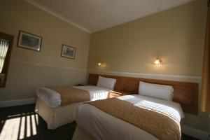 A bed or beds in a room at Grange Moor Hotel