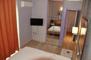 A television and/or entertainment centre at Eva Hotel Piraeus